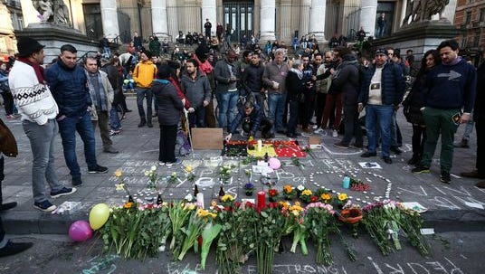 People gather to leave tributes at the Place de la Bourse following attacks on March 22, 2016, in Brussels. At least 31 people are thought to have been killed after Brussels Airport and a subway station were targeted by explosions. The attacks come just days after a key suspect in the Paris attacks, Salah Abdeslam, was captured in Brussels.