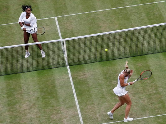 Serena Williams of the U.S, left, returns to Timea Babos of Hungary, right, and Yaroslava Shvedova of Kazahkstan, not pictured, during her women's doubles final with playing partner Venus Williams of the U.S on day thirteen of the Wimbledon Tennis Championships in London, Saturday, July 9, 2016. (AP Photo/Ben Curtis)