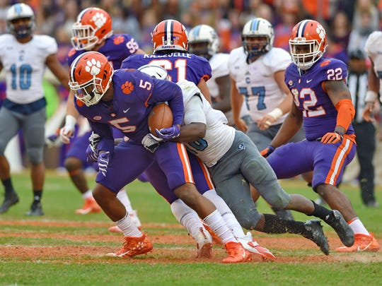 Clemson's Tee Higgins drags Citadel's Cam Jackson while gaining a first down during the second half of an NCAA college football game Saturday, Nov. 18, 2017, in Clemson, S.C. Clemson won 61-3. (AP Photo/Richard Shiro)