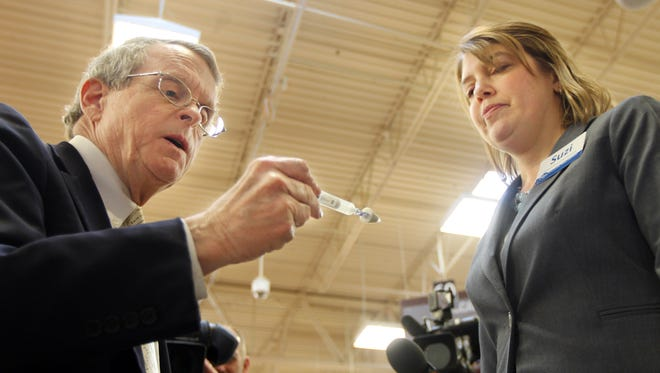 Mike DeWine, Ohio Attorney General, examines an atomizer used to administer naloxone, a drug that counteracts the effects of an opioid overdose. At right is Suzi Francis, a pharmacist and clinical care coordinator for Kroger, which announced Friday that it will provide naloxone without a prescription.  The announcement was made at the Oakley Kroger store.