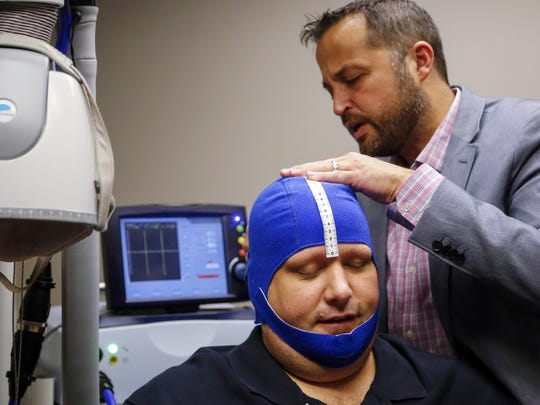 Dr. Eric Barlow of Compass Clinical Associates prepares Daniel Finney for his first session of transcranial magnetic stimulation Tuesday, Oct. 6, 2015.