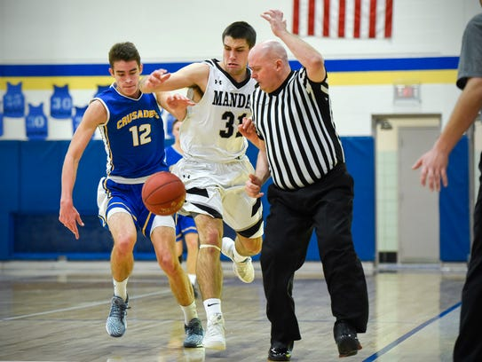 Cathedral's Mitchell Plombon, 12, and Mandan's Trae Steckler battle for a loose ball during the first half Thursday, Dec. 28, in the Crusaders Christmas Classic at Cathedral High School.