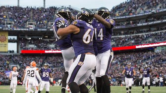 Baltimore Ravens wide receiver Kamar Aiken (11) celebrates with guard John Urschel (64) and wide receiver Marlon Brown (14) after scoring a touchdown during the fourth quarter against the Cleveland Browns at M&T Bank Stadium.