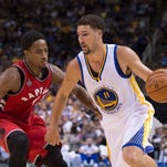 Golden State Warriors guard Klay Thompson (11) dribbles the basketball against Toronto Raptors guard DeMar DeRozan (10) in a recent game.