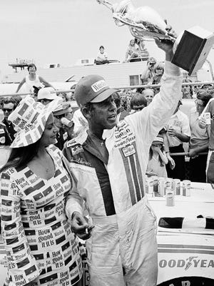 David Pearson waves his Firecracker 400 trophy after his narrow victory over Richard Petty at Daytona International Speedway on July 5, 1974. Pearson's win was his third consecutive in the  Daytona summer race.