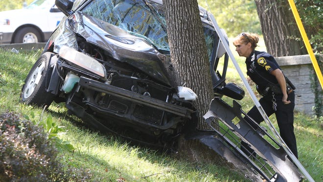 Police Specialist Cristen Schircliff looks over the wreckage of the car, which was eastbound on Lafayette Avenue.