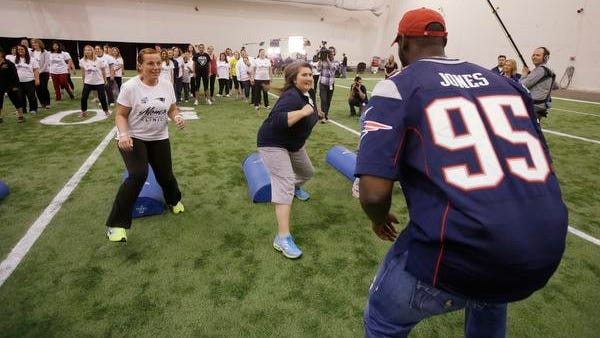 In this May 29 photo, New England Patriots defensive end Chandler Jones coaches participants during a football safety clinic for mothers in Foxborough, Massachusetts. The mothers are learning about tackling techniques, hydration, training and equipment care, all designed to help their sons play the game safely.