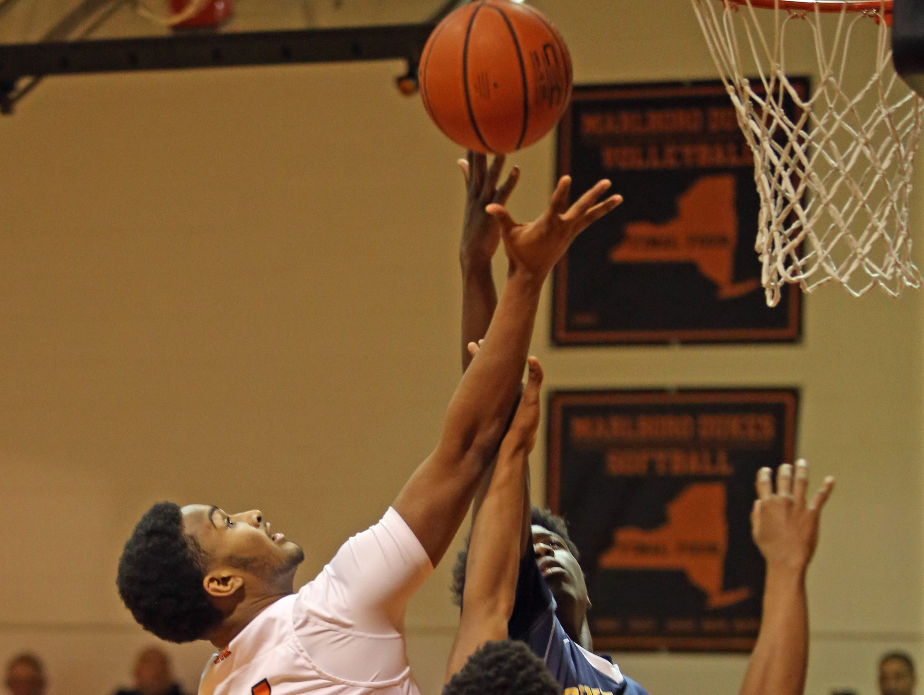 Marlboro's Billy Williamson (14) goes up for two over Pine Bush's Keon Gill (12) and D' Alton Dixon (44) during boys basketball game at Marlboro High School Jan. 9, 2017.
