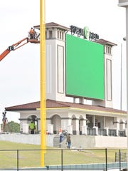 Workers tend to details on the new scoreboard Tuesday at Joker Marchant Stadium in Lakeland, Florida.