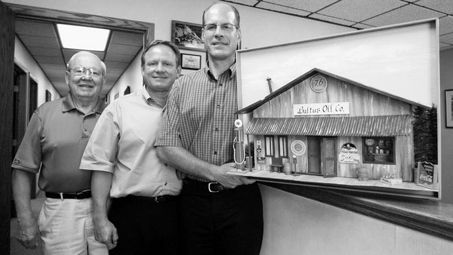 Vern Baltus, far left, poses with his sons, John, center and Frank at the Baltus corporate offices in Marshfield with a piece of art representing their business. Vern Baltus died Friday.