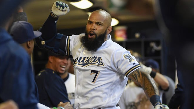 The Milwaukee Brewers' Eric Thames celebrates in the dugout after hitting a two-run home run in the third inning against the Pittsburgh Pirates at Miller Park.