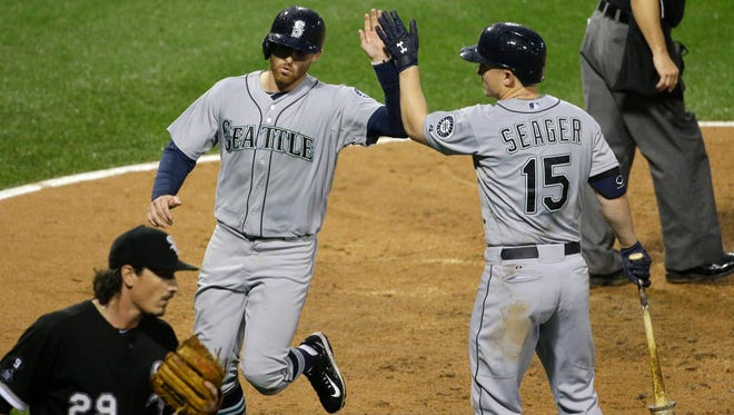 Seattle Mariners' Brad Miller, left, celebrates with Kyle Seager after scoring on a sacrifice fly by Ketel Marte as Chicago White Sox starter Jeff Samardzija reacts during the fourth inning of a baseball game Saturday, Aug. 29, 2015, in Chicago.