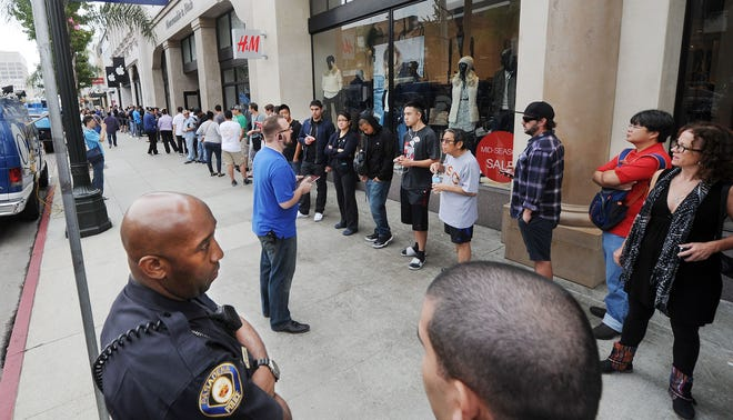 An Apple worker in Pasadena,  Calif., addresses the crowd waiting to purchase new iPhones on Sept. 20, 2013.