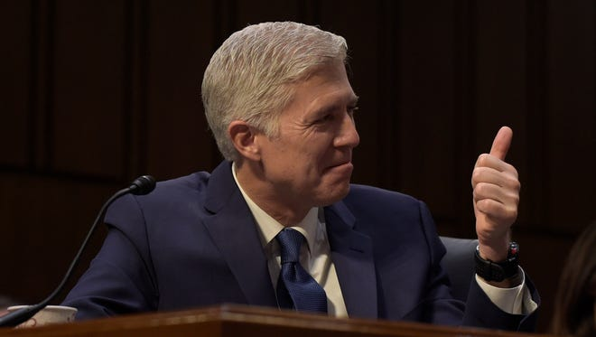 Supreme Court Justice nominee Neil Gorsuch gives a thumbs-up when asked how he is doing as he listens to opening statements on Capitol Hill in Washington on Monday during his confirmation hearing before the Senate Judiciary Committee.