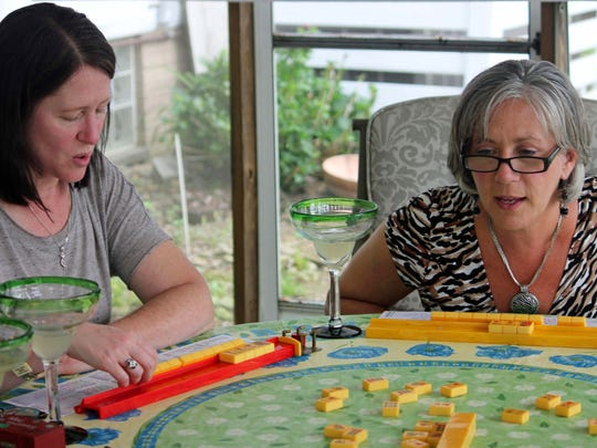 Debbie Schwartz, left, and Marcy Imperi playing mahjong during a game night gathering in Mayfield Village, Ohio. For the baby boomer generation, getting together to play games is a way to stay active and social. It also can help people stay mentally sharp.