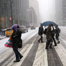 The first flakes of what's forecast to be a historic blizzard coat the streets of Midtown Manhattan on Monday afternoon.