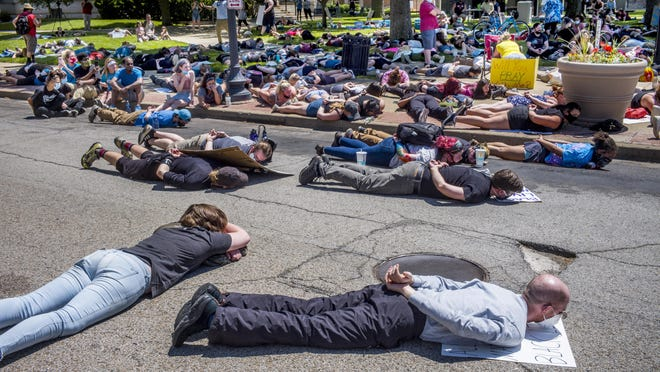 Protesters lie down for 8 minutes and 46 seconds, representing the time George Floyd was handcuffed on the ground by police May 25 in Minneapolis before he died, at a rally supporting Black Lives Matter in Pekin on Saturday. About 200 protesters gathered at the corner of South Capitol and Court streets in Pekin at the Tazewell County Courthouse.