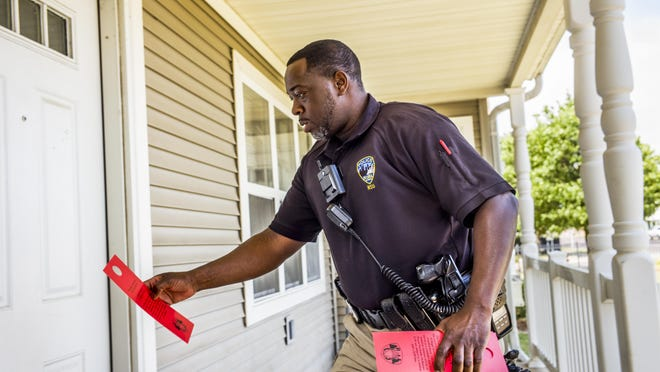 Peoria Police Department neighborhood police officer James Hodges steps up to door in the Riverwest apartment complex while distributing information on the City of Peoria's fireworks ordinance Friday. Hodges has been hanging the placards on apartment doors in the days leading up to Fourth of July holiday in areas of the city that have had issues in the past with non-compliance with the ordinance.