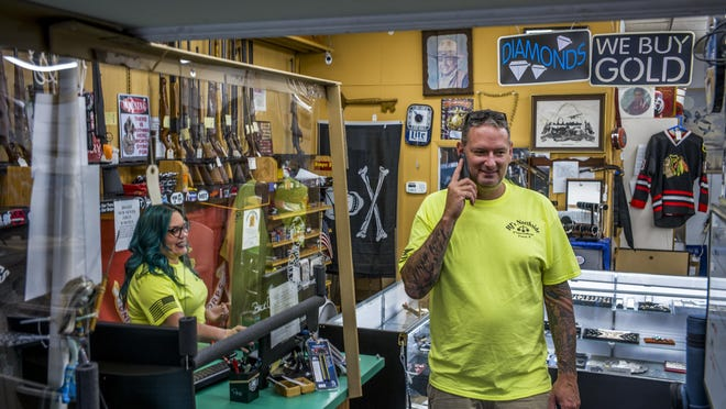 """R & J's Northside Pawn Shop owner Sean Smith takes a call at the Peoria shop Thursday, July 16, 2020 as sales consultant Mollee Wood works at the counter. Employees often face odd financial interactions with customers, including """"moist money,"""" cash customers pull from their underwear."""