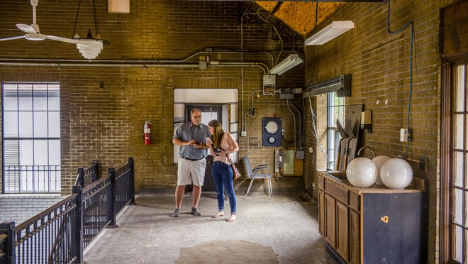 Pete Clarno and his daughter Erica Ogden share information as they stand in the former Peoria Heights water works building at 1201-1203 East Kingman Ave. on June 30. Clarno, his wife, Linda, and Ogden will be turning it into a popcorn and candy store.