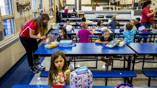 Jefferson Elementary School principal Kate Wyman, left, helps students spaced out for lunch at the Morton school Friday, August 14, 2020.