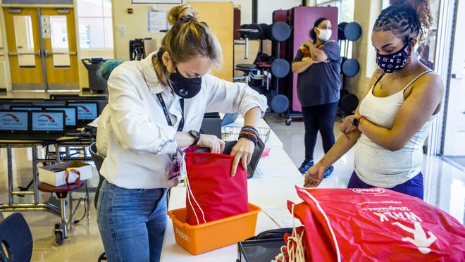 Harrison Community Learning Center teaching assistant Ksenia Efimova, left, slides a laptop into a bag Friday, August 21, 2020 during dispensation of remote learning equipment to students and their families.