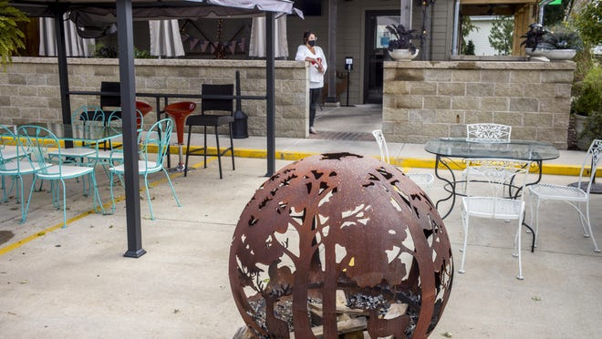 Owner Diane Feuchter stands in one of several outdoor seating areas at Pizza 150 in Kickapoo on Sept. 17. Feuchter and other restaurant owners are trying to make plans to maintain outdoor dining and other amenities for the coming fall and winter season. At Pizza 150, that includes a fire pit, foreground, with multiple covered and spaced outdoor table areas.