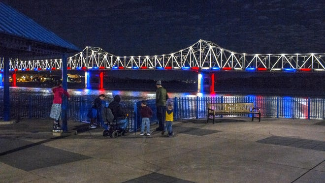 A family gathers in East Peoria to view the lights illuminating the Murray Baker Bridge over the Illinois River Saturday, October 31, 2020.