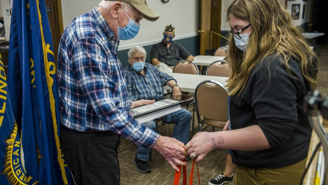 Limestone High School JROTC member Kenzie Jadd, 15, offers a gift to U.S. Air Force veteran Bruce Stewart, left, Monday, November 9, 2020 at American Legion Post 2 in Peoria as a commemoration of Veterans Day. The tradition is coordinated by The Fuller Center to each year recognize veterans.