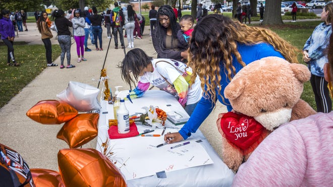 Brooklyn Parker, with a large stuffed bear in hand, finishes writing a note to honor her friend Diamond Williams on Monday, Sept. 28, 2020.