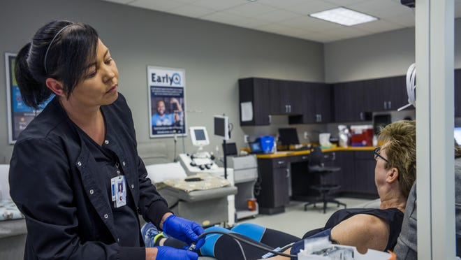 Christina Mosley, phlebotomist in charge of the Mississippi Valley Regional Blood Center in Peoria, prepares blood donor Marilyn Shork for the process Wednesday, January 22, 2020.
