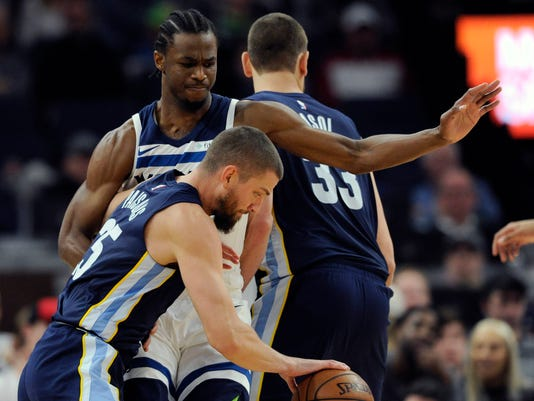 Minnesota Timberwolves' Andrew Wiggins (22) guards against Memphis Grizzlies' Chandler Parsons (25) during the second quarter of an NBA basketball game on Monday, March 26, 2018, in Minneapolis. (AP Photo/Hannah Foslien)