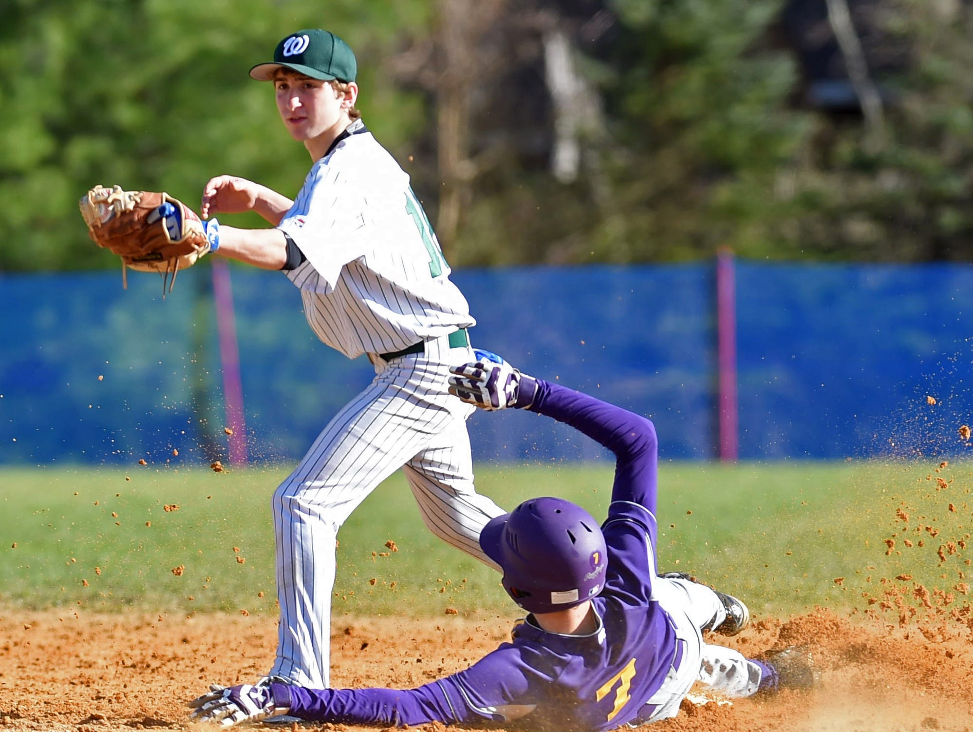 Rhinebeck's Aidan Hack slides into second base under Webutuck's Chris Milano during Wednesday's game at Rhinebeck.