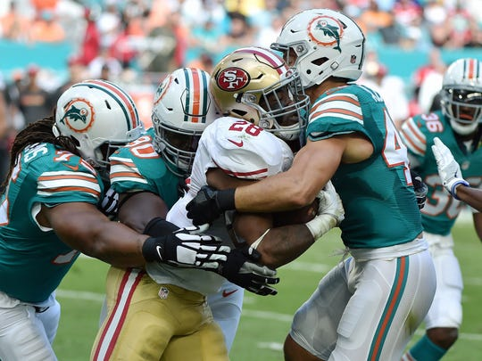Nov 27, 2016; Miami Gardens, FL, USA; San Francisco 49ers running back Carlos Hyde (center) is tackled by Miami Dolphins defensive tackle Earl Mitchell (90) during the first half at Hard Rock Stadium. Mandatory Credit: Steve Mitchell-USA TODAY Sports