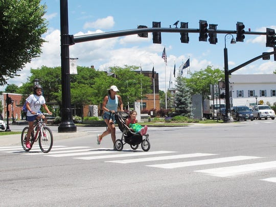 Lily Boutin, 11, at left, bicycles across Five Corners in Essex, in the company of her mother, Courtney Boutin, and sister, Isabella Boutinm, 6.