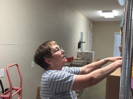 Volunteer Joan Laszewski stocks shelves at the new Mt. Juliet Help Center building.