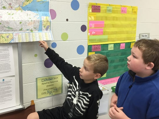 Keegan McAfee, left, and Andrew Romer, right, look at a map sent by New Jersey's Thad Livingston, who has become the school's adopted grandfather.