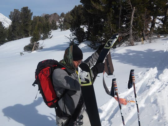 Peeling skins off skis before a low-angle descent to