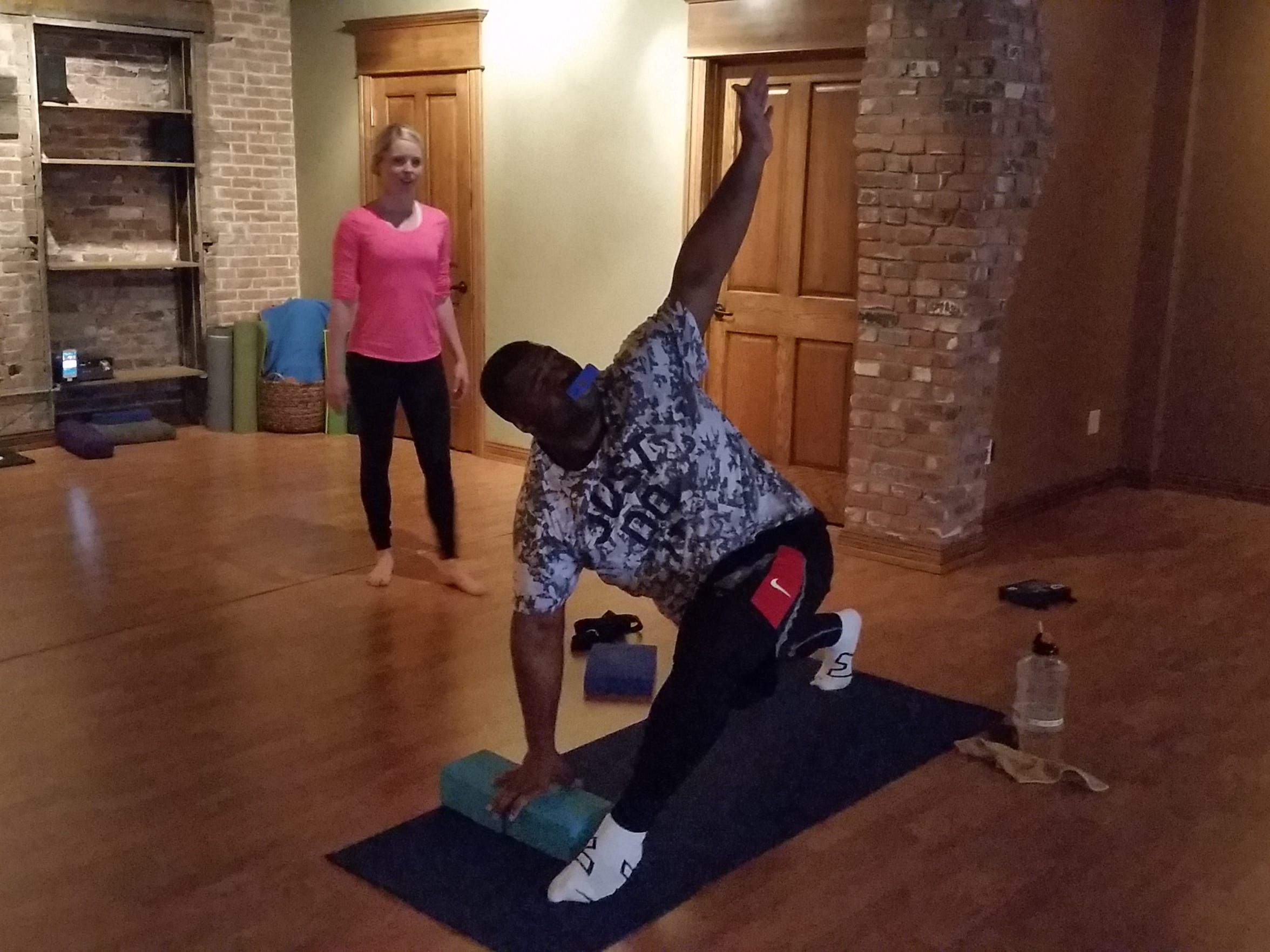 Packers defensive lineman B.J. Raji stretches his shoulder, spine and hamstring during a yoga session Friday at Flow Yoga Studio in De Pere. Instructor Ryanne Cunningham looks on.
