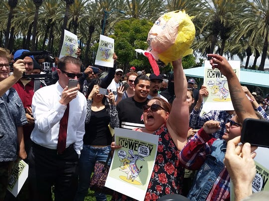 A woman raises the fake severed head of Donald Trump outside the Anaheim Convention Center on May 25, 2016. Trump's appearance drew protests.