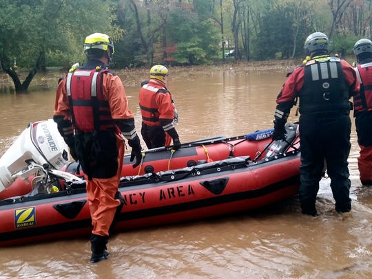 A rescue team on a flooded McIntyre Way, in Trout Run,