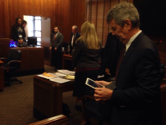 Nashville attorney Tom Dundon holds a tablet to communicate