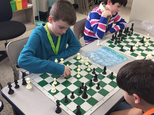 Noah Vaughn, near left, plays chess with Cody Ambrose, right at Mt. Juliet Elementary. Bryce Christenson, far left, plays in another game as part of the school's chess club.