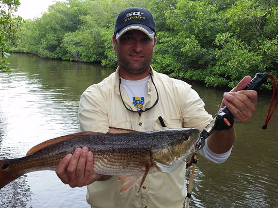 Adam L. Neal shows a 24-inch redfish he caught in 2016 while kayak fishing in the Indian River Lagoon