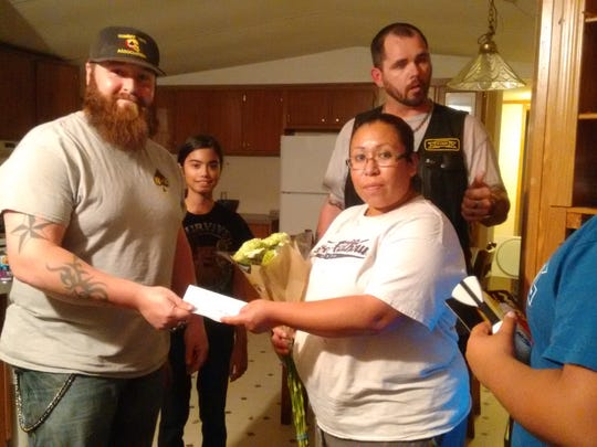 Edward Meyer, CVMA volunteer presents a check of $550 to pay her rent.