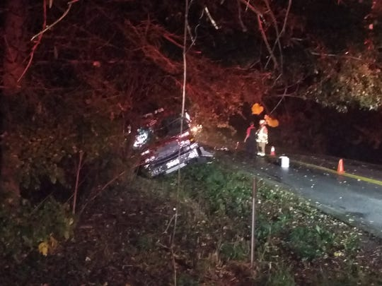 Emergency personnel stand beside a town of Delafield fire truck caught in a ditch after it crashed at about 2 a.m. Oct. 14 on Silvernail Road. The four firefighters on board all suffered minor injuries.