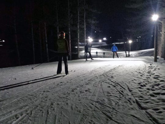 Skiers make their way down a small hill on the lighted