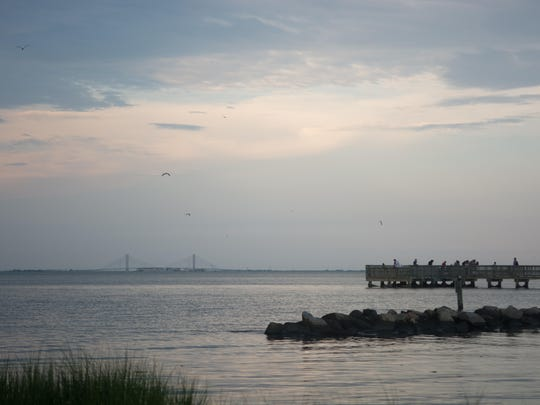 Folks gather at the Holts Landing State Park fishing pier to catch crabs.