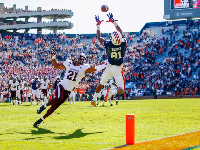 Auburn wide receiver Darius Slayton (81) leaps for a catch as Texas A&M Aggies defensive back Charles Oliver (21) defends during the second half of an NCAA college football game, Saturday, Nov. 3, 2018, in Auburn, Ala. (AP Photo/Todd Kirkland)