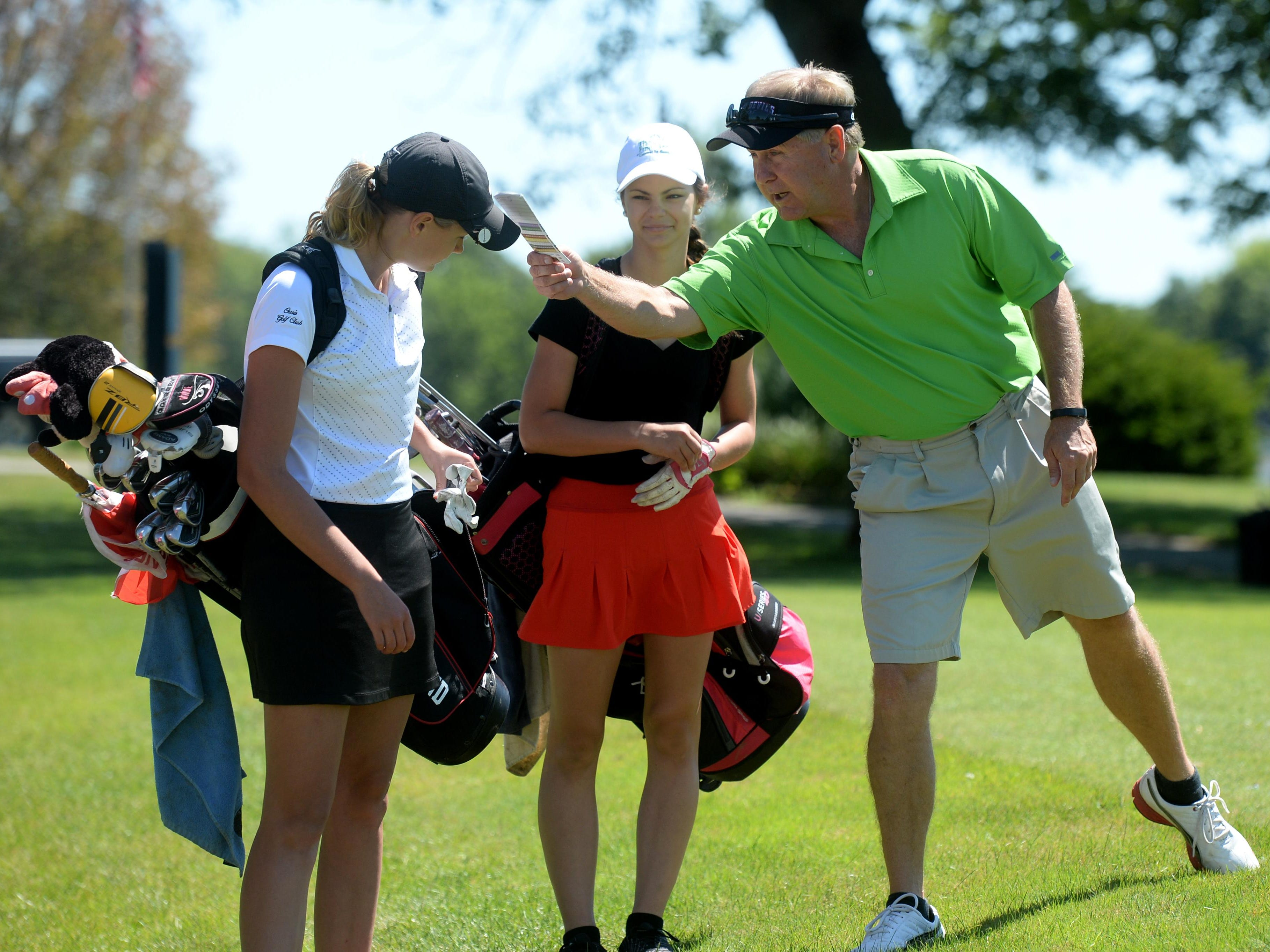 Richmond High School golf coach Ron Murphy, right, jokes with golfers Jacey Cornett, left, and Maggie Camp during practice at Elks. This is Murphy's final season as the Red Devils golf coach.